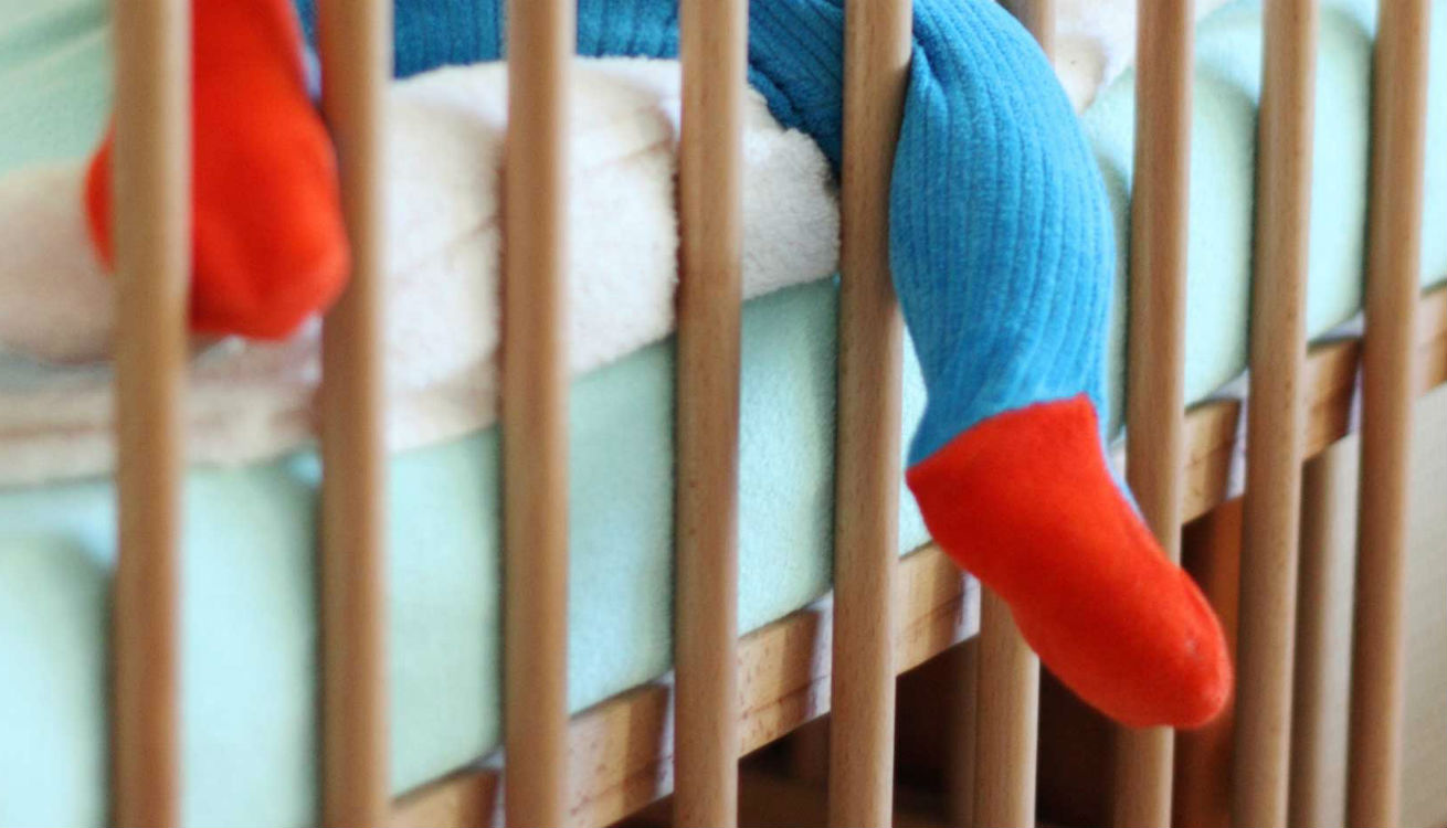 Baby feet poking through gaps between cot bars