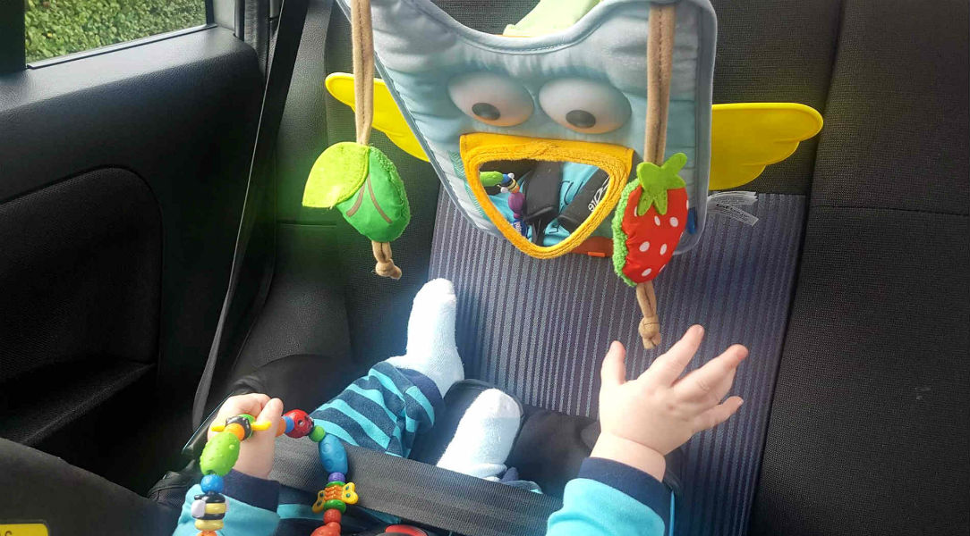 Max keeping occupied in his rear facing car seat with the Taf Toys Musical Owl Car Seat Toy