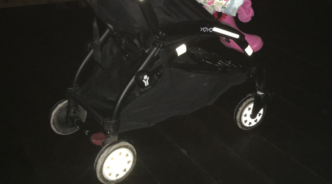 Amelie riding in her buggy with the Pogu Reflective Wheel Stickers