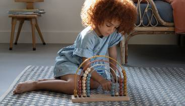 A girl counting with the Little Dutch Rainbow Abacus.