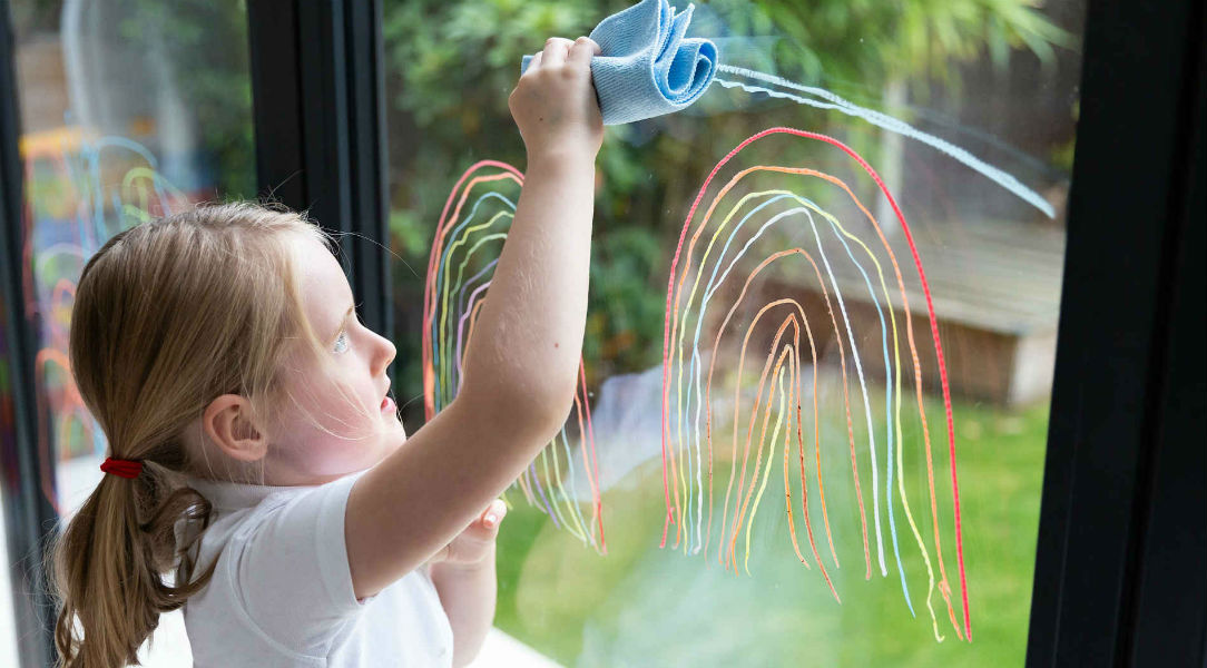 Girl wiping Kitpas crayons off window