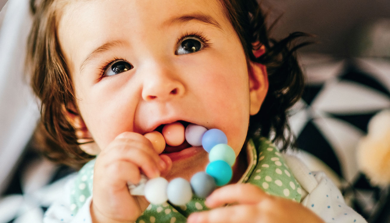 Baby girl chewing on Blossom & Bear Rainbow Teething Ring