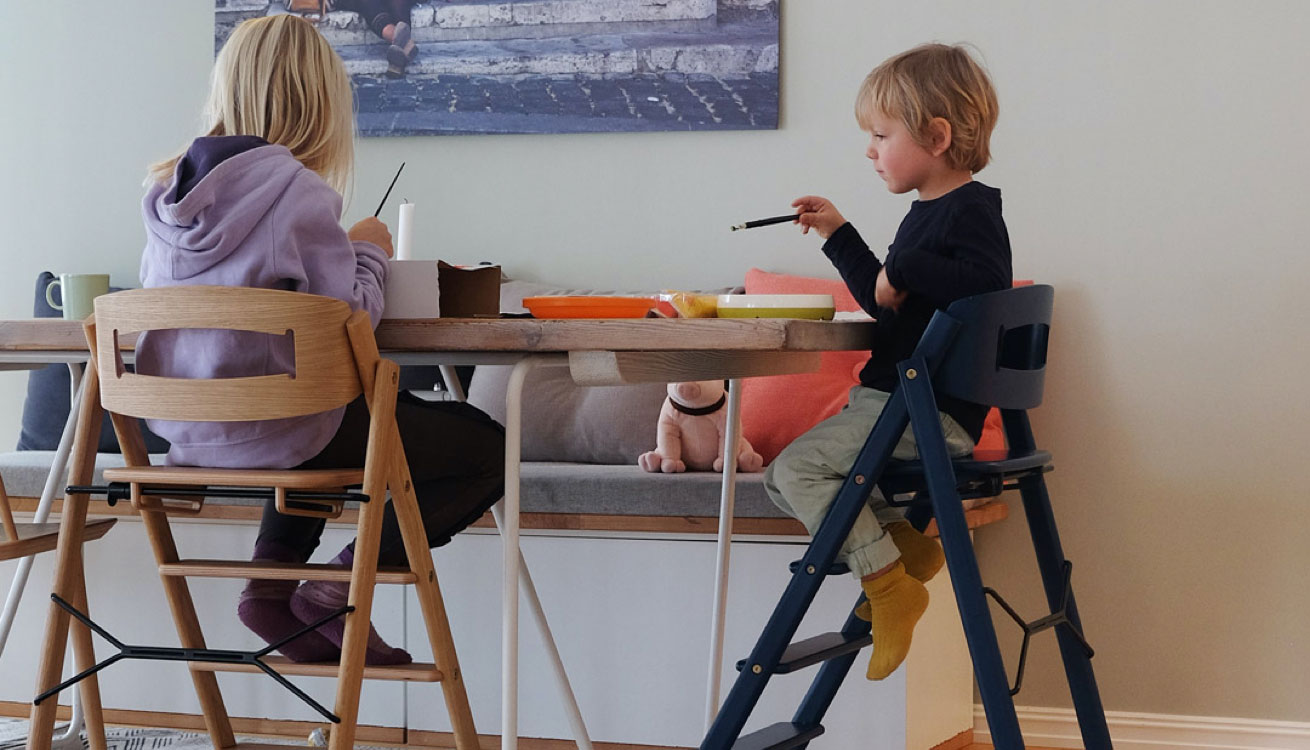 Two kids sitting in the KAOS Klapp Foldable Highchairs