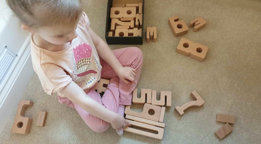 Girl playing with Sumblox Math Wooden Building Blocks