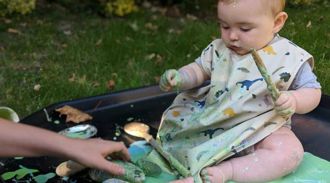 baby playing with messy green substance guided by an adult