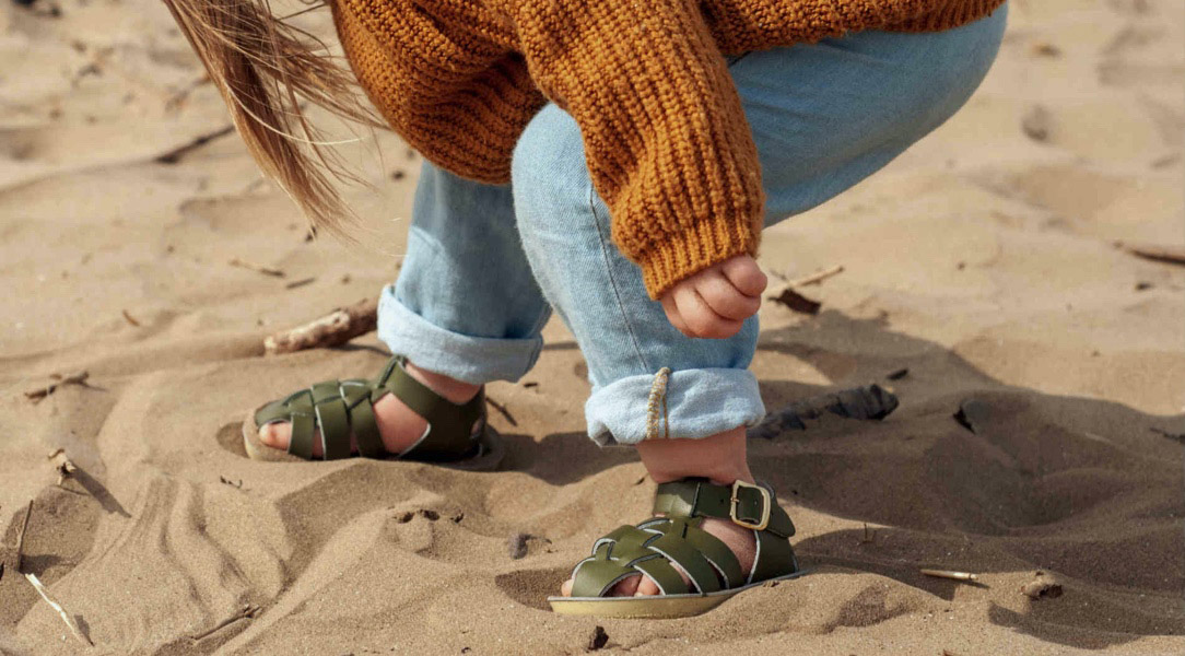 girl in green sandals on sand