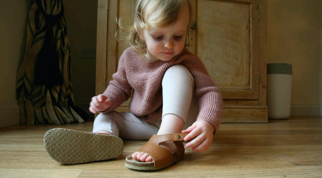 little girl putting on brown sandal