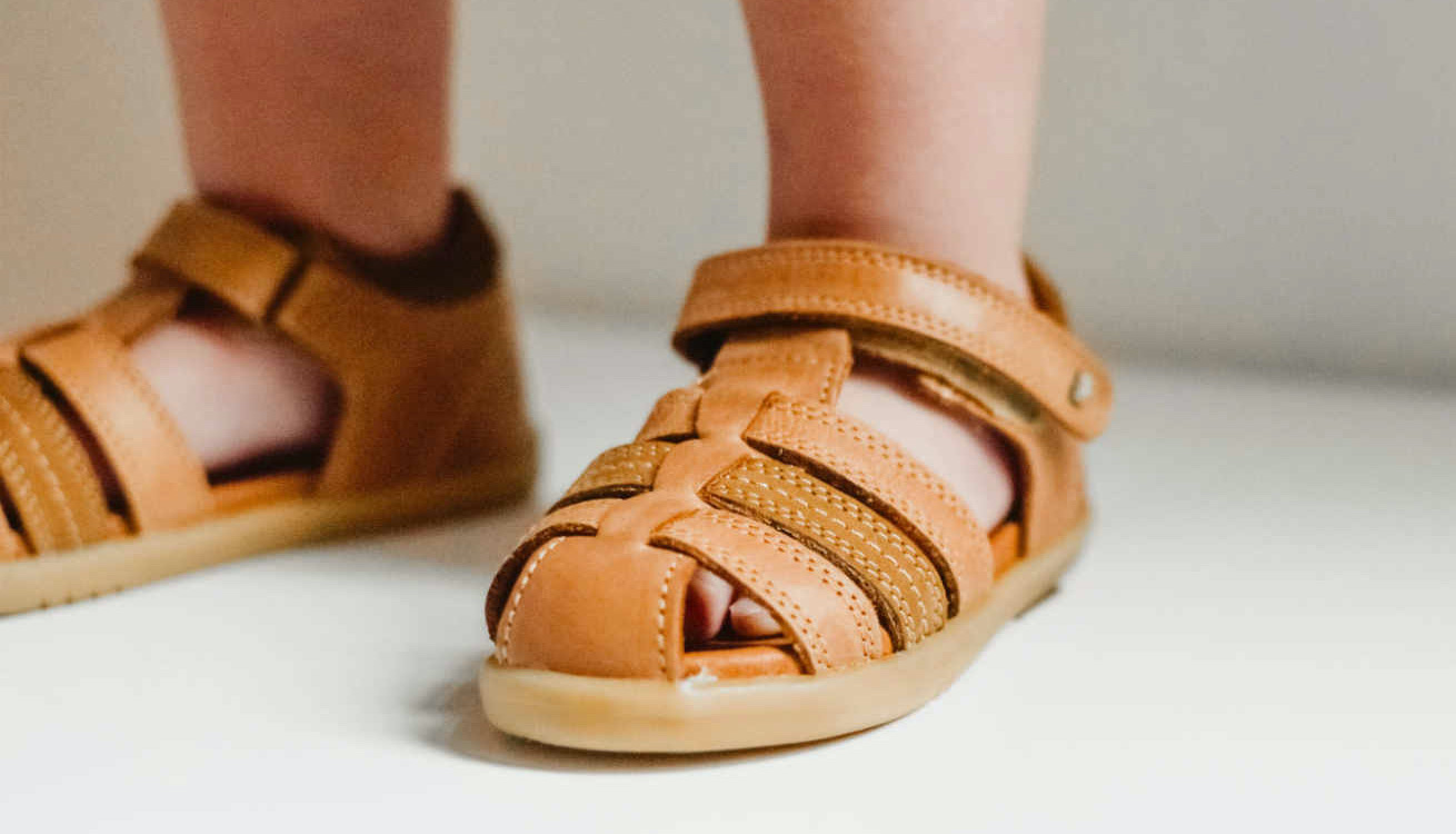Toddler standing in tan-coloured summer sandals