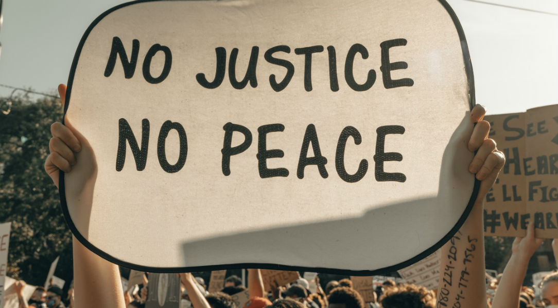 banner saying: NO JUSTICE NO PEACE