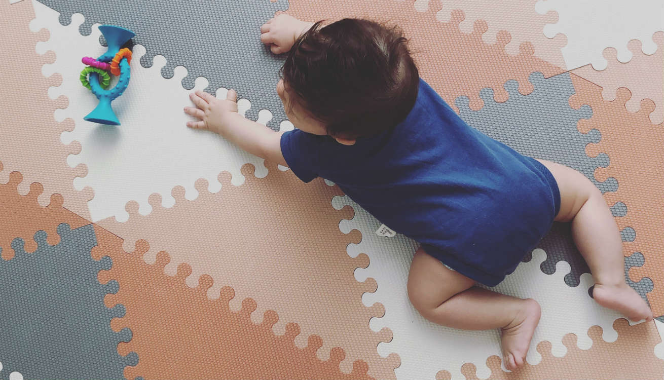 Baby crawling on the Skip Hop Playspots Foam Floor Tiles