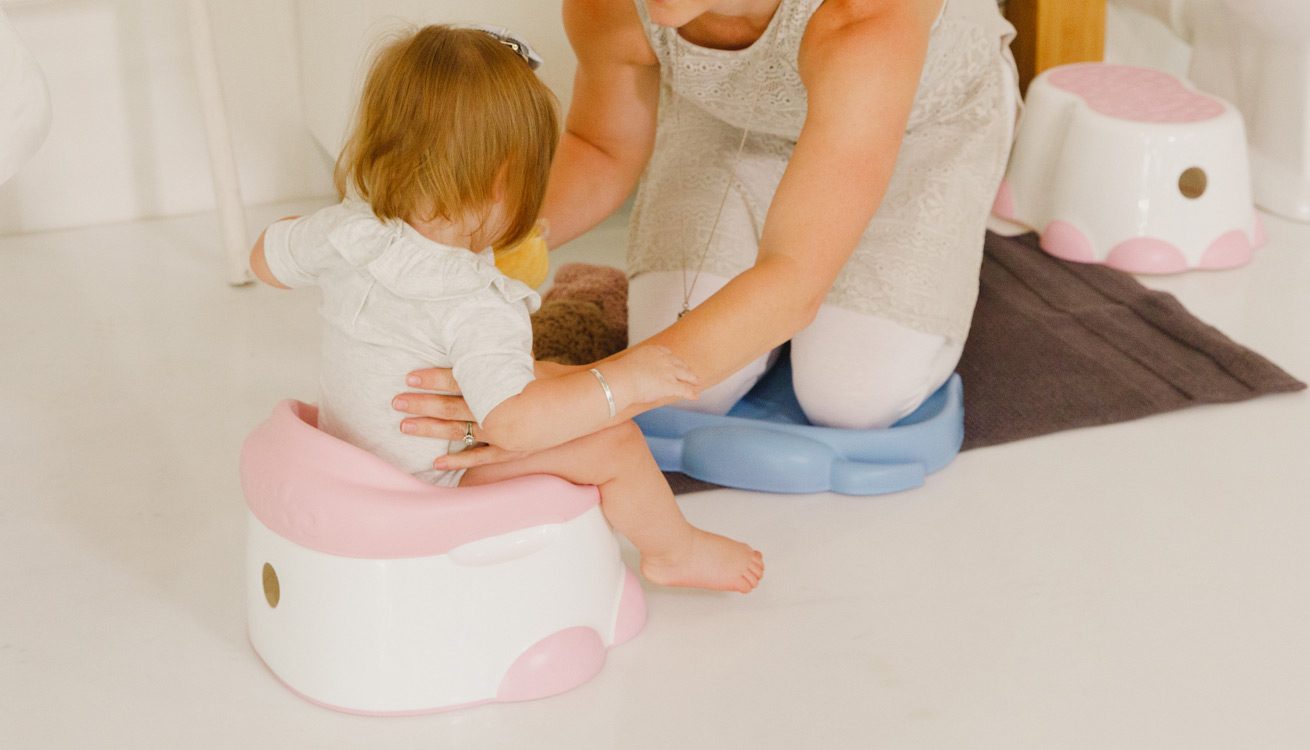Toddler sitting on a Bumbo potty
