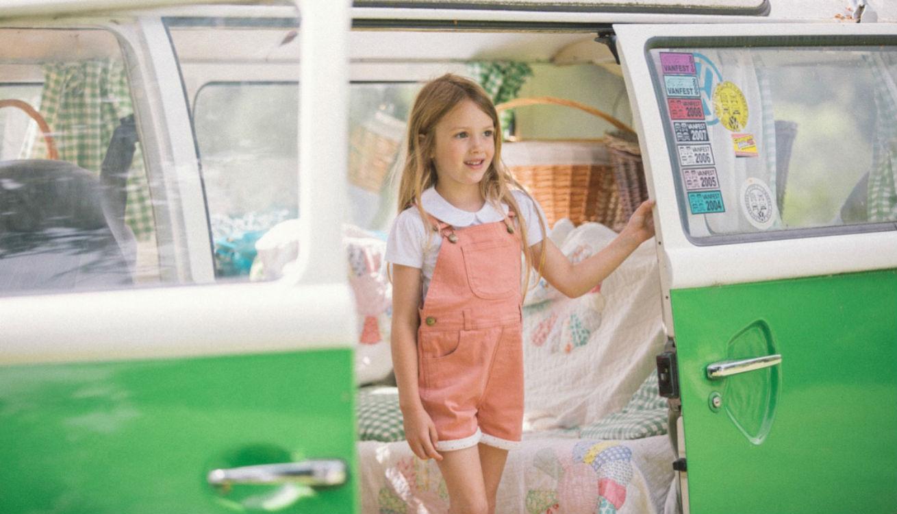 Girl in Dotty Dungarees in camper van
