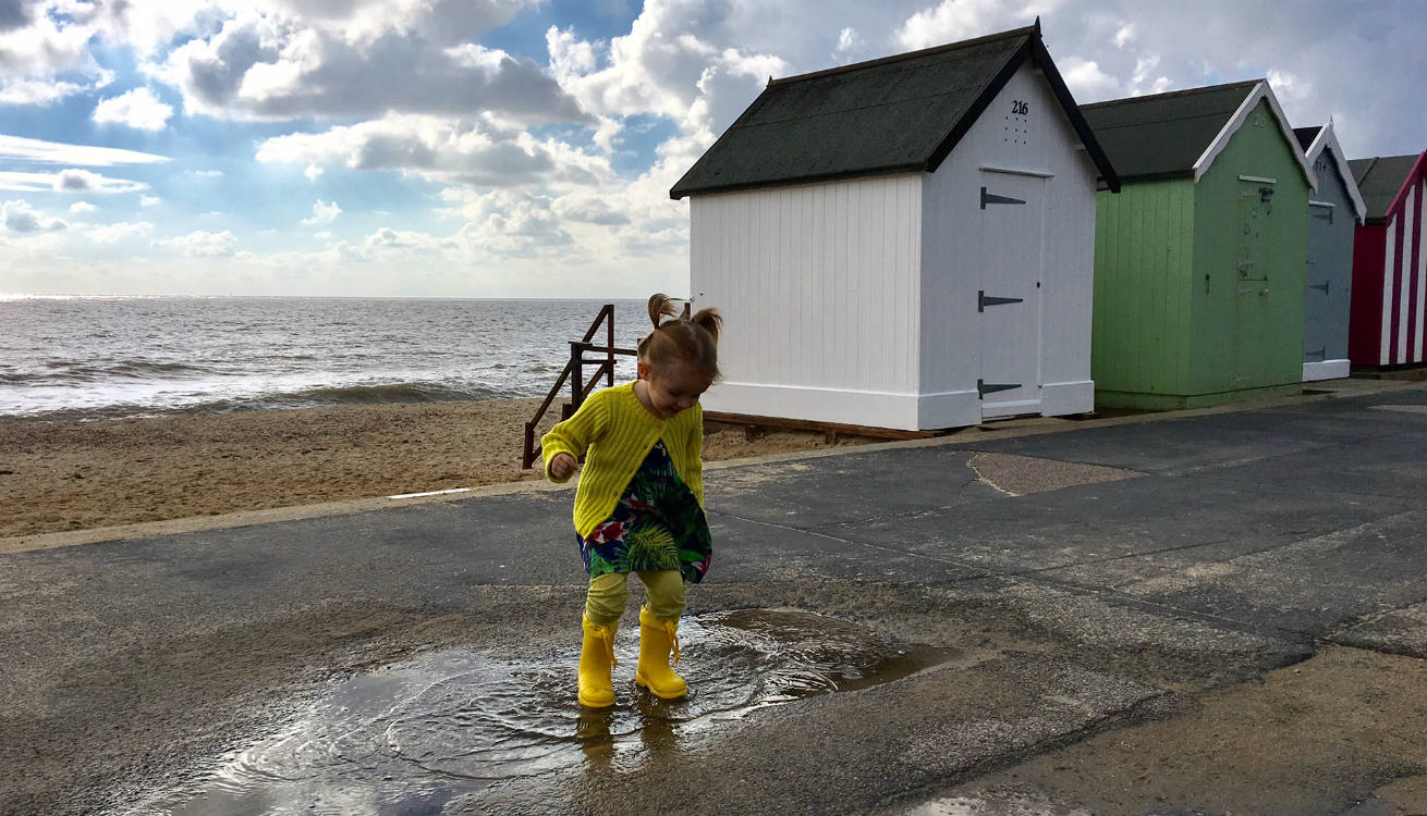 Girl jumping in puddles at the beach