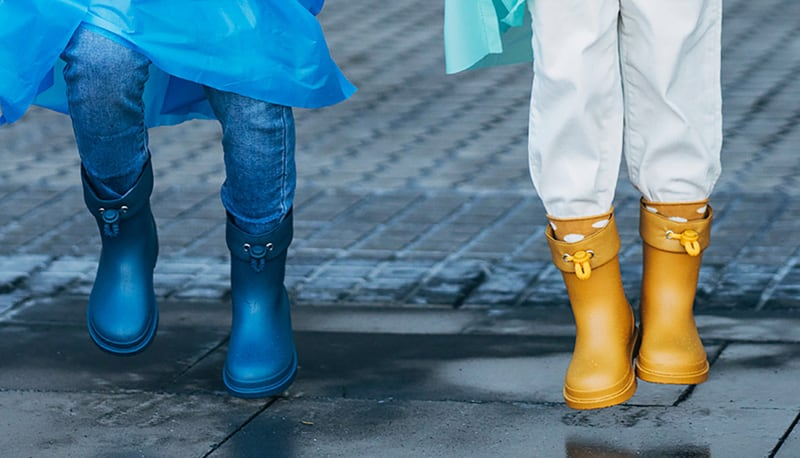 Two young kids wearing jumping in puddles