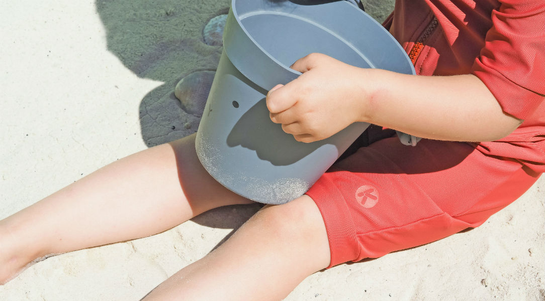 boy in swim trunks and rash vest sitting in sand holding bucket