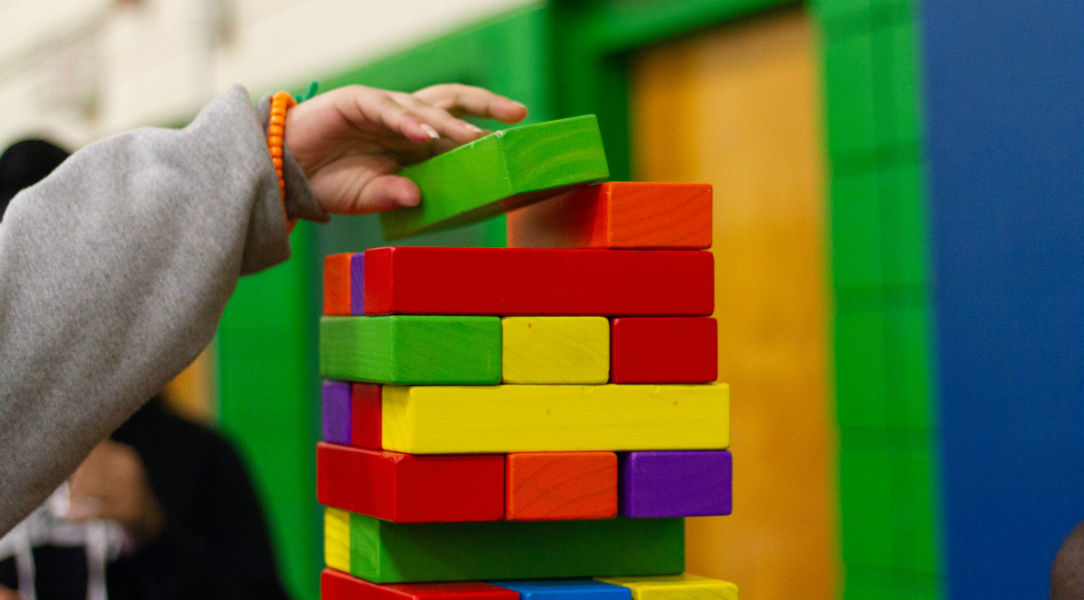 Unseen child building a tower of Jenga-style blocks