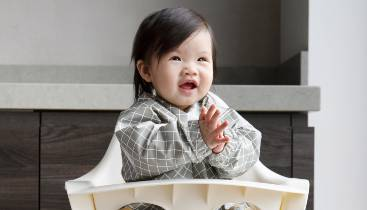 Kiara clapping in her KIDLY Label Coverall Bib