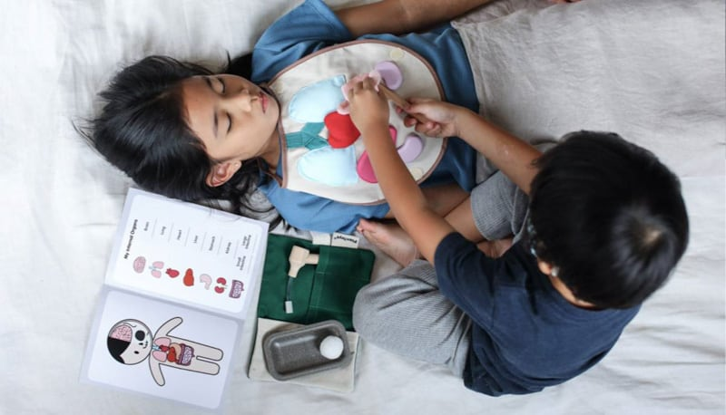 Two children playing with the Plan Toys Surgeon Set