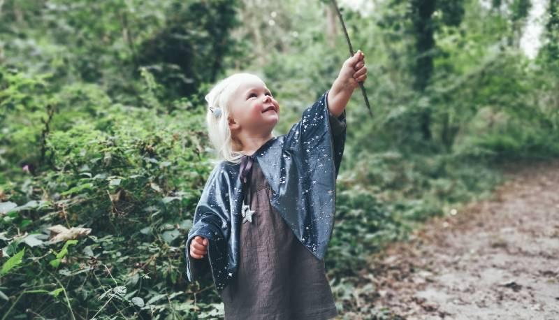 Penny wearing Meri Meri Velvet wizards cape in the woods