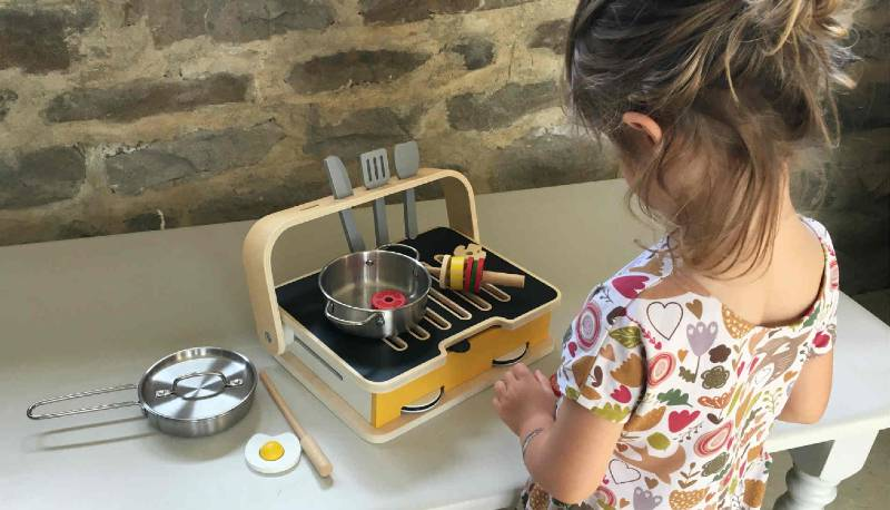 Little girl playing with the Classic World 2 In 1 Tabletop Kitchen