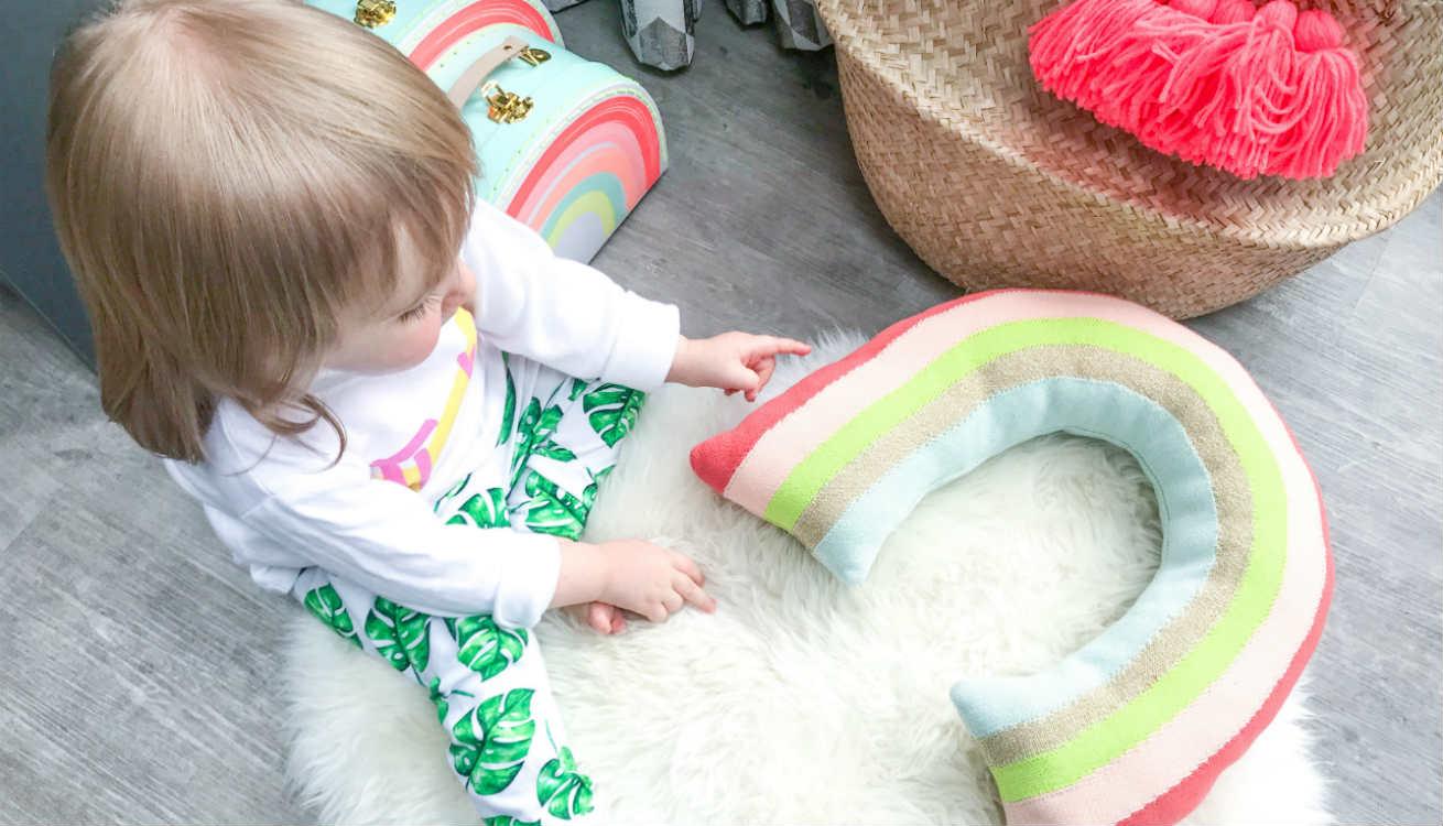 Thalia testing out the Meri Meri rainbow cushion and retro rainbow suitcases