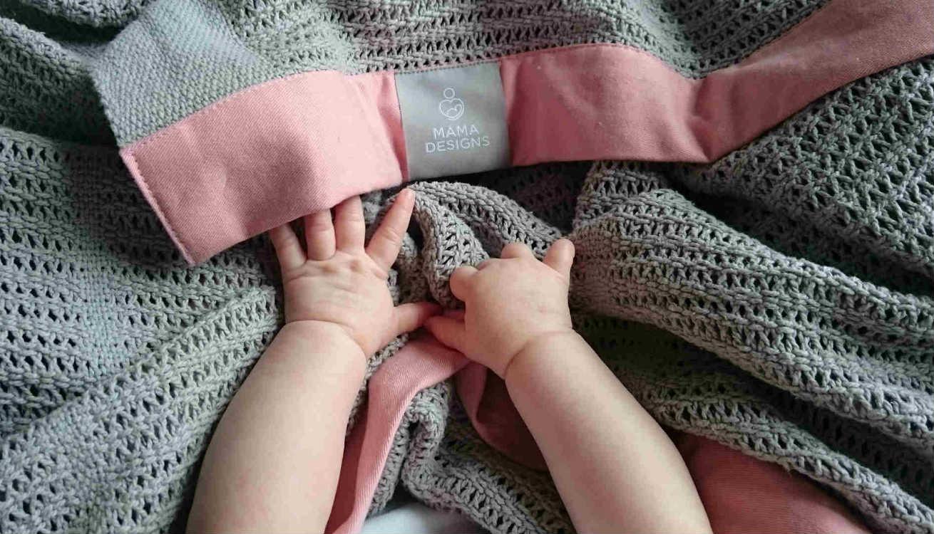 Rhaya snuggled in the Mama Designs Cellular Blanket