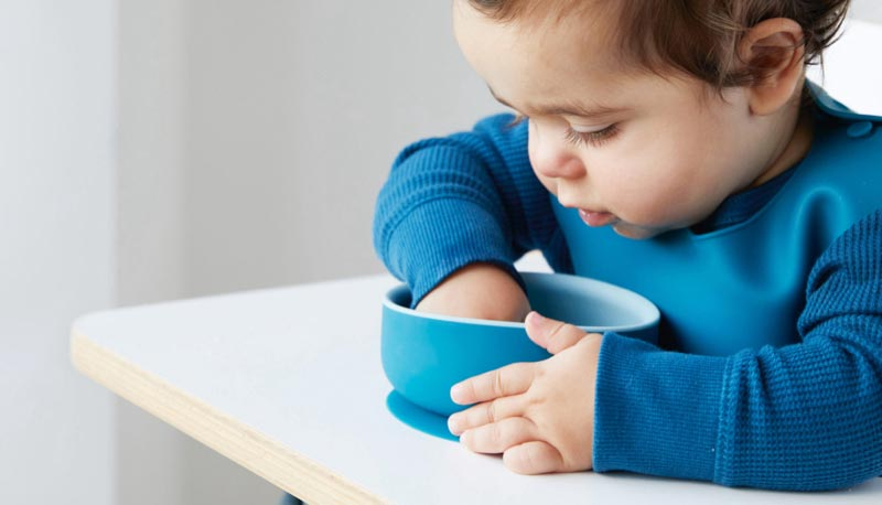Baby Hudson scooping food out of his KIDLY Label Suction Bowl
