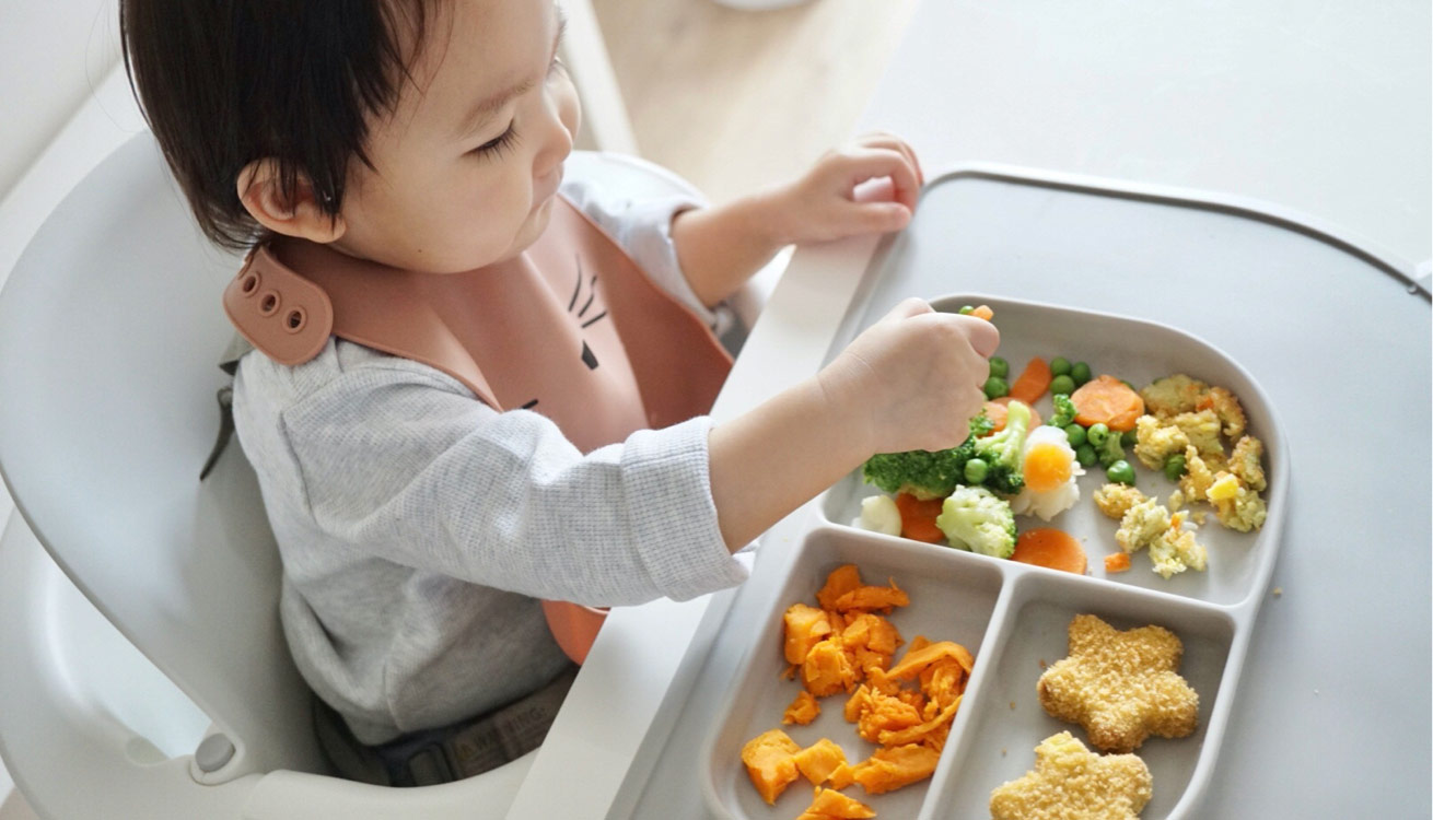 Toddler happily eating using a sectioned Liewood Oliver Placemat