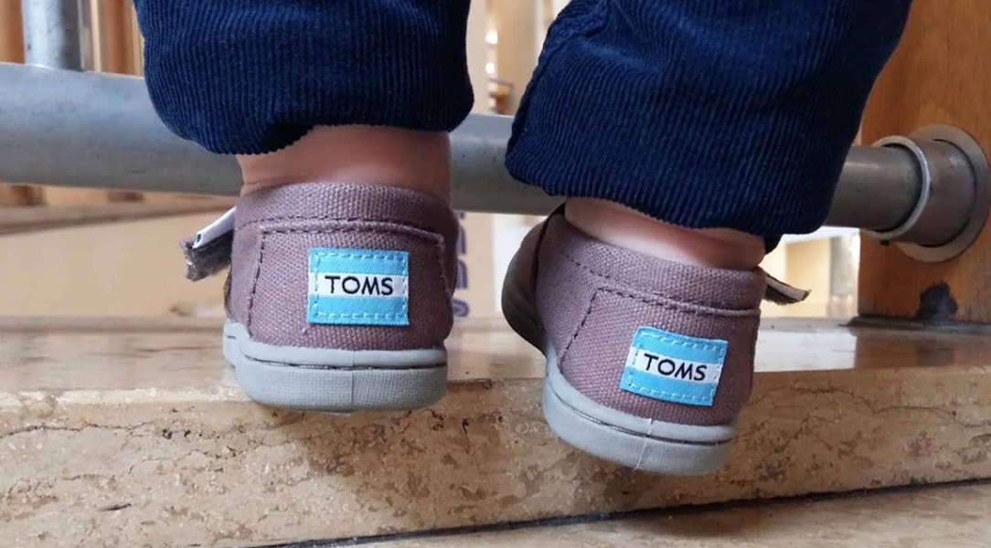 Monty's feet stay cool and dry in his comfy TOMS classic canvas Plimsolls