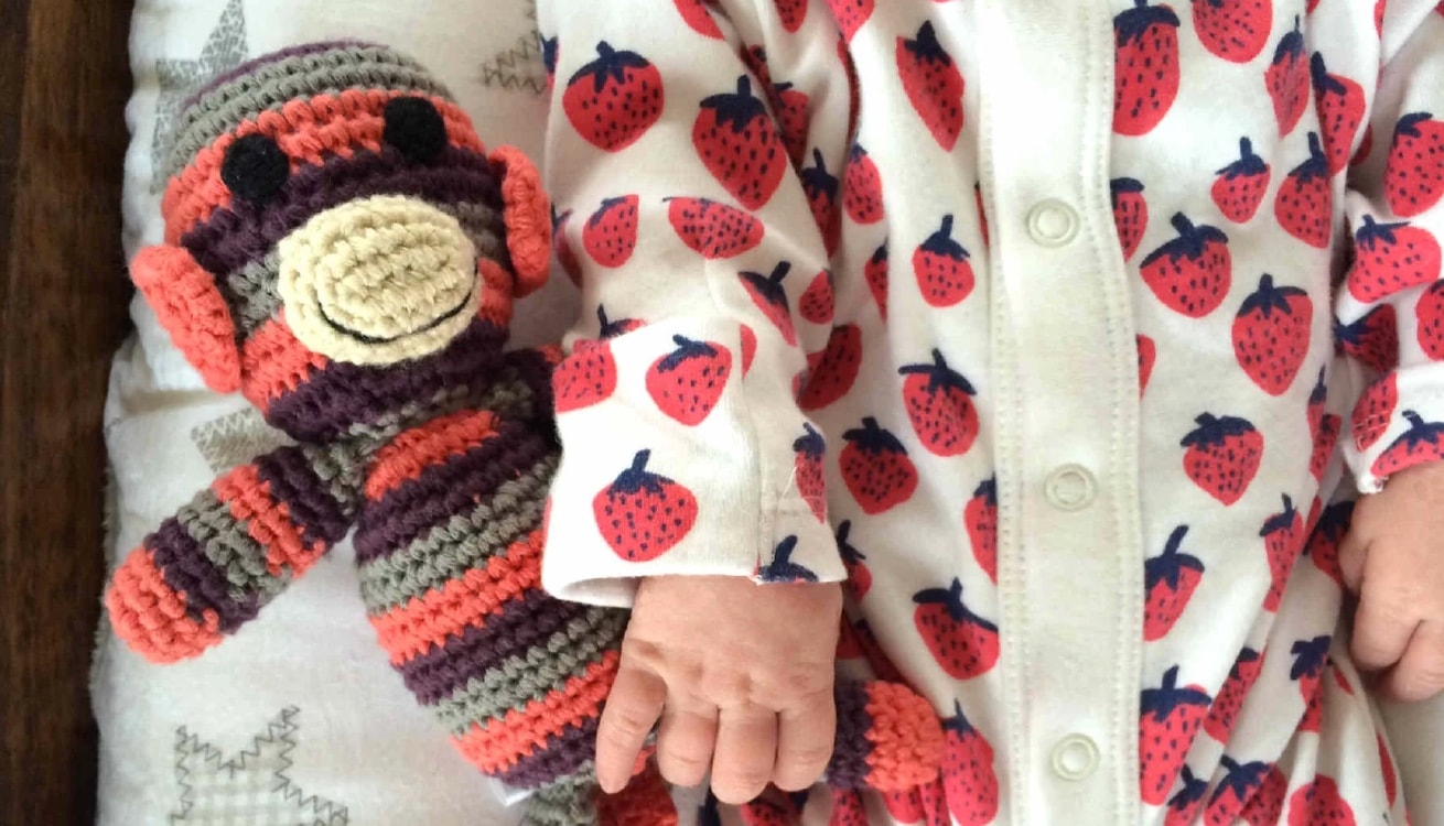 Amelie holding onto her Pebble Monkey Crochet Rattle