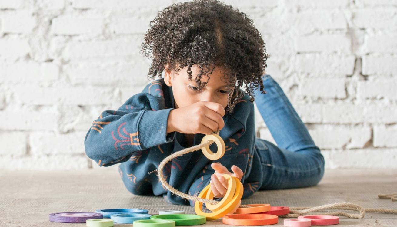 Child playing with coloured wooden rings