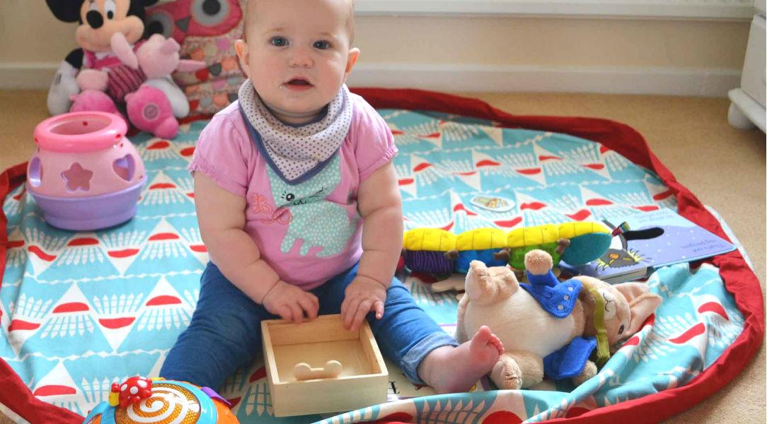 Georgia sitting on her Play & Go storage bag mat