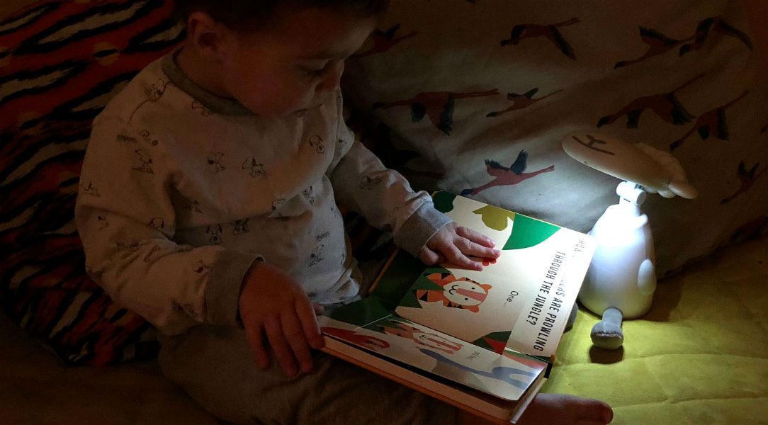 Van reads his book under the light of the Zazu Fin Nighlight