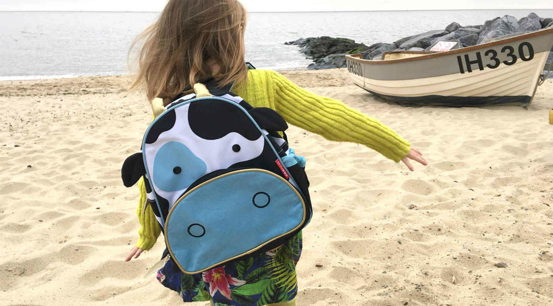 Elsa runs on the beach while wearing her Skip Hop Zoo Kids backpack
