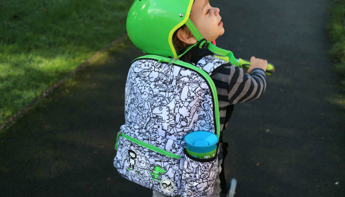 Oscar wears his Babymel Dino Print backpack while riding his Globber scooter to preschool.